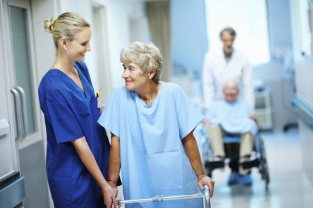 Happy nurse and doctor assisting a woman and man with a walker and wheelchair