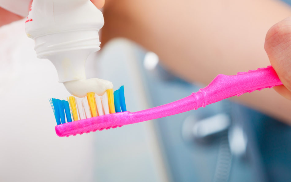 Dental health care. Closeup woman hands is holding toothbrush and placing toothpaste on it.